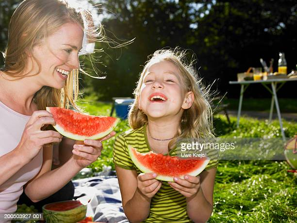 Mother and daughter (6-8) eating watermelon at picnic