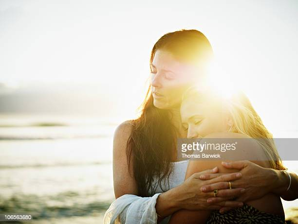 Mother and daughter embracing at sunset