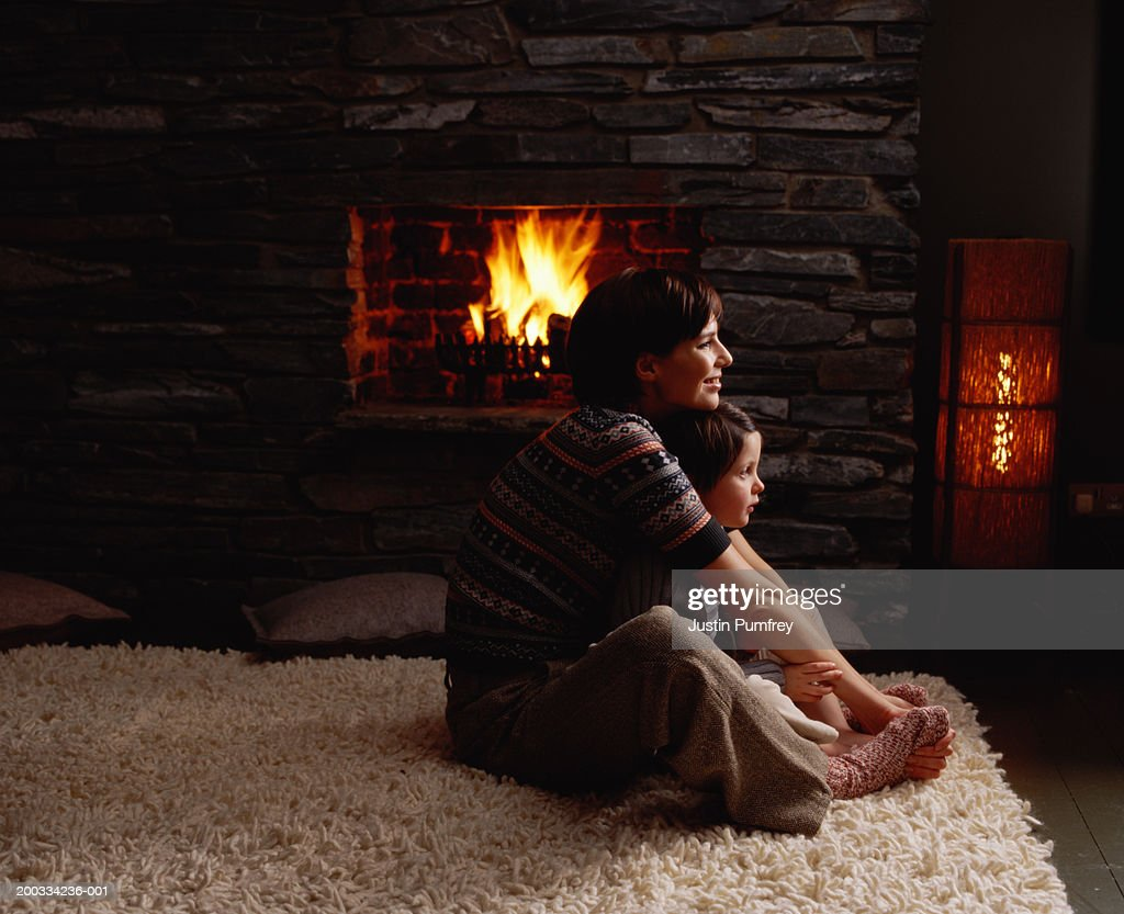 Mother and daughter (4-6) embracing by fireplace, side view