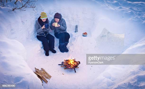 Mutter und Tochter genießen Sie eine heiße Schokolade an einer Feuerstelle.