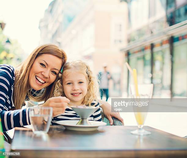 Mutter und Tochter genießen Sie Eiscreme im Freien.