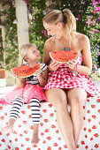 Mother And Daughter Enjoying Slices Of Water Melon