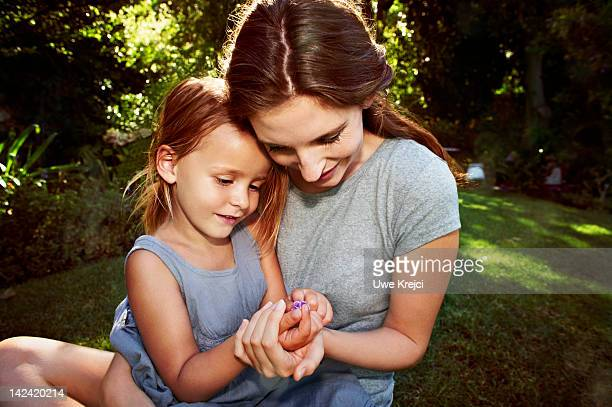 Mother and daughter examining flower