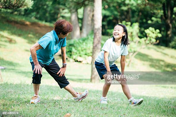 Mother and daughter exercising and stretching in Yoyogo Park, Japan