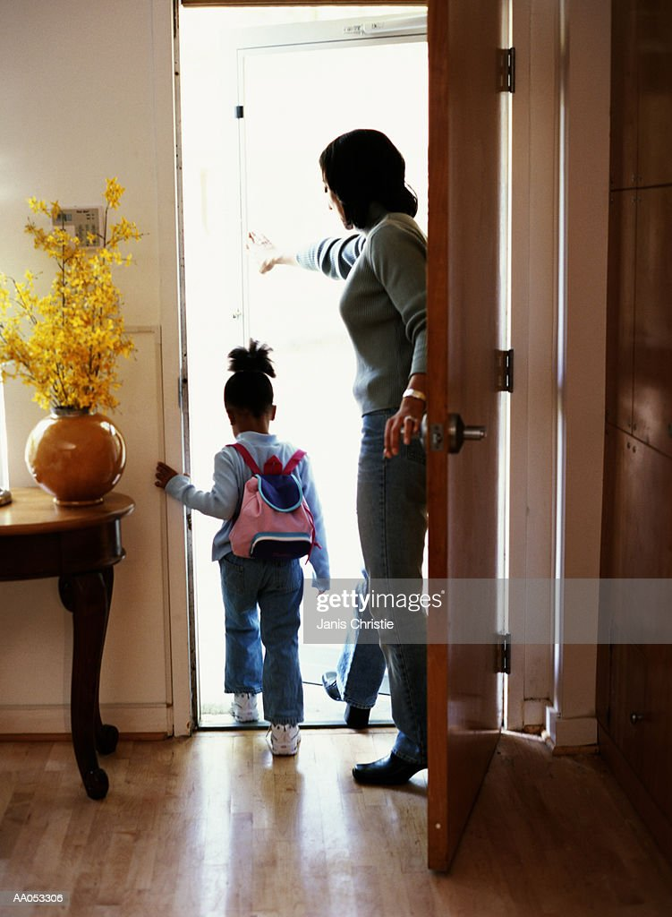 Mother and daughter (3-5) exiting door of house, rear view