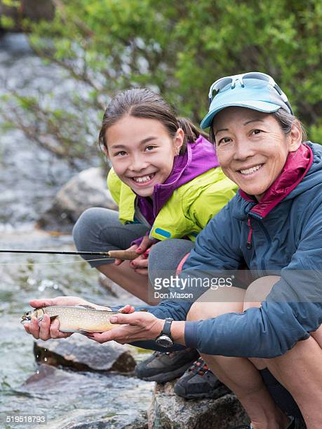 Mother and daughter fishing in river