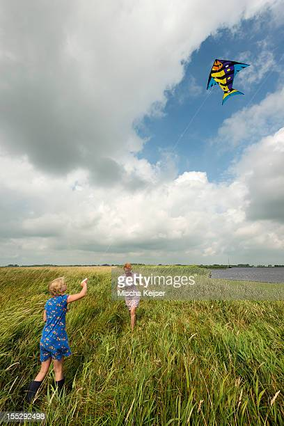 Mother and daughter flying kite in field