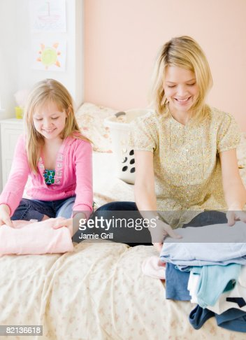 Mother and daughter folding clothing