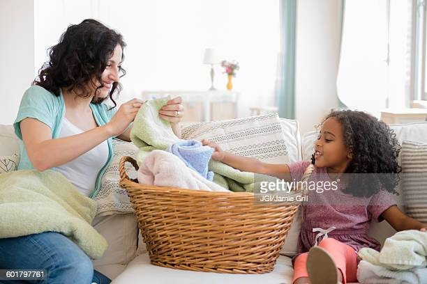 Mother and daughter folding laundry
