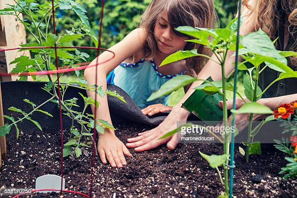 Mother and daughter gardening in a small space outdoors.