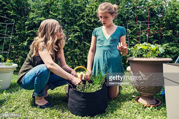 Mother and daughter gardening in backyard outdoors.