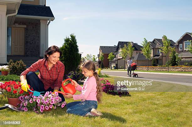 Mother and daughter gardening in yard