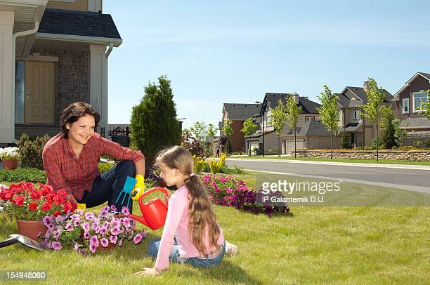 Mother and daughter gardening on  the front yard