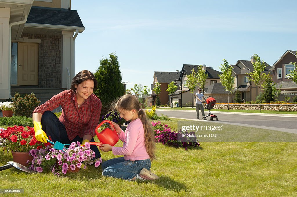 Mother and daughter gardening while father walks with baby