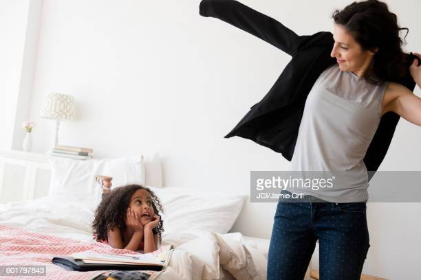Mother and daughter getting ready in bedroom