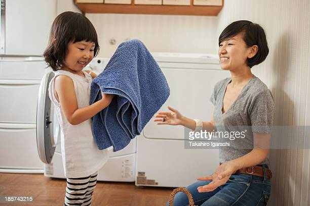 Mother and daughter,  girl folding towel