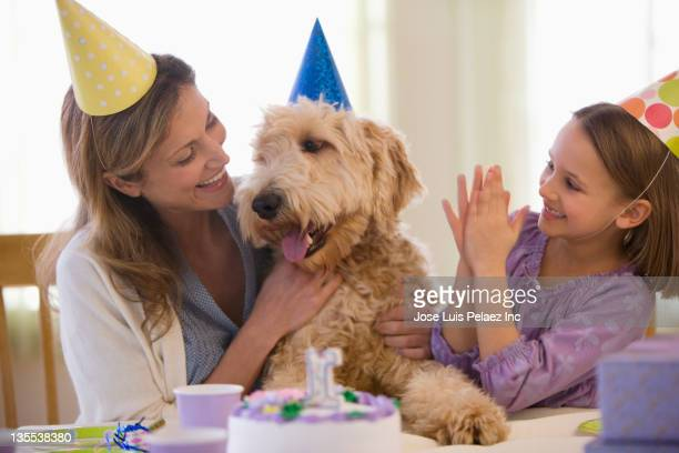 Mother and daughter giving dog birthday party