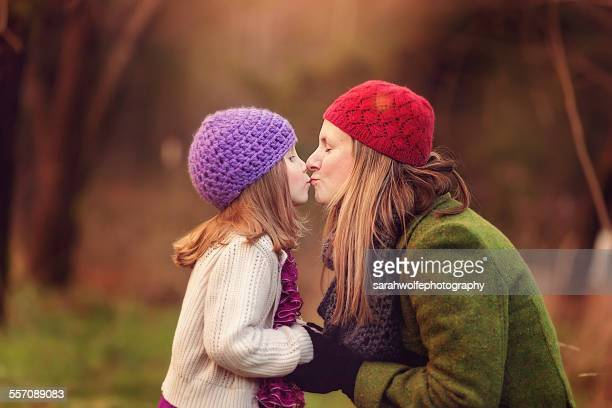 mother and daughter giving each other a kiss