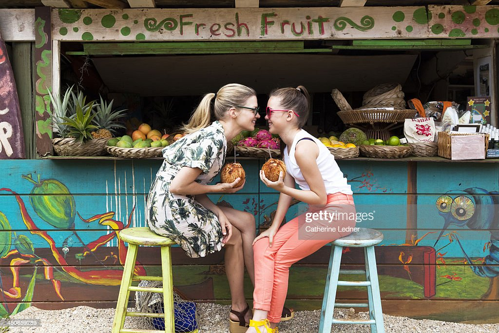 Mother and daughter goofing around at fruit stand : Stock Photo