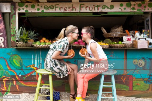 Mother and daughter goofing around at fruit stand