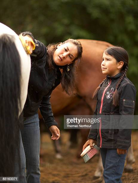 Mother and daughter grooming horse