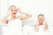 Mother and daughter had a day of spa. They are in white bath towels with slices of cucumber on their eyes.