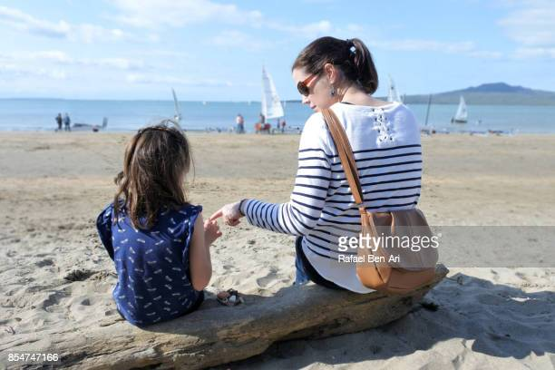 Mother and daughter having a conversation on the beach