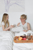 Mother and daughter having breakfast in bed