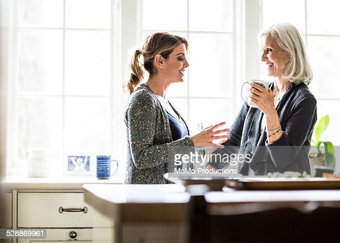 mother and daughter having coffee in kitchen
