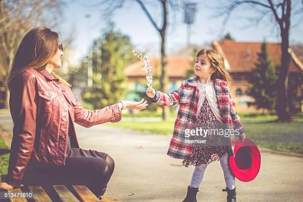 Madre con hija tiene diversión en otoño parque