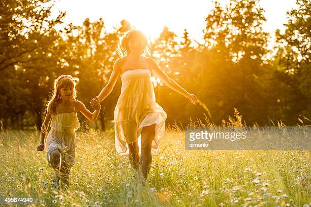 Mother and daughter having fun in forest at sunset