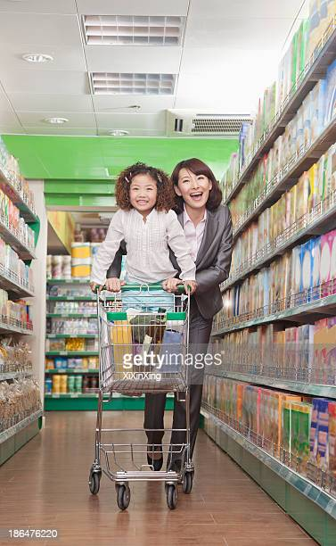 Mother and Daughter Having Fun in Supermarket, Pushing Cart