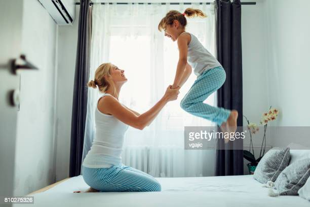 Mother and Daughter having fun in the morning in their bed