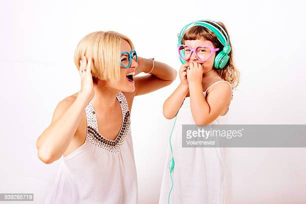 Mother and daughter having fun listening music