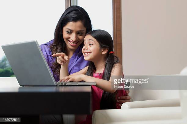 Mother and daughter having fun on a laptop