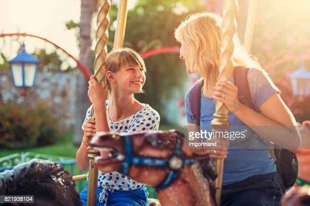 Mother and daughter having fun on carousel ride