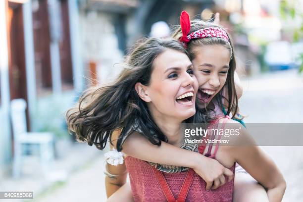 Mother and daughter having fun on street
