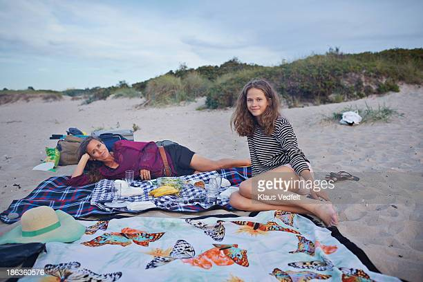 Mother and daughter having picnic at beach