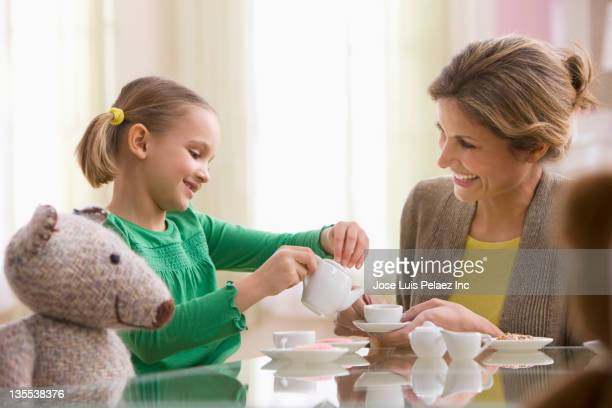 Mother and daughter having tea party