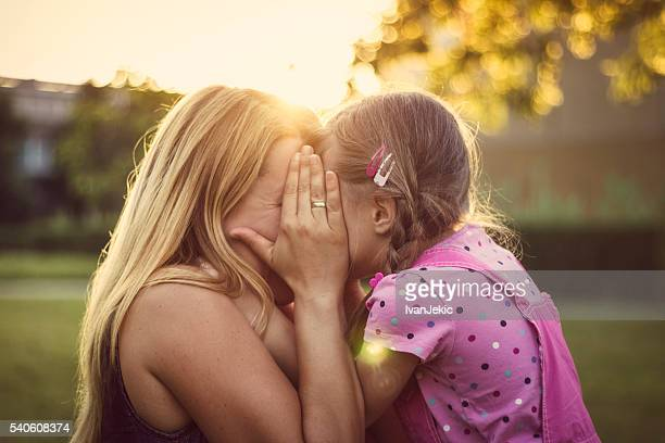 Mother and daughter hiding behind the hand