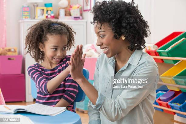 Mother and daughter high-fiving during homework in playroom