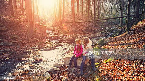 Mother and daughter hikers resting in a forest by stream