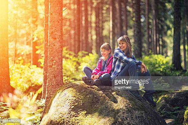 Mother and daughter hikers resting in a forest.