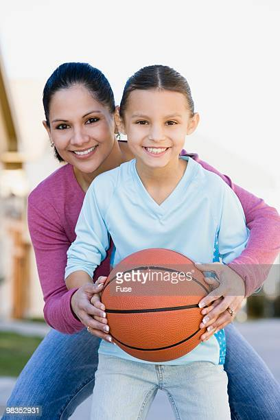 Mother and daughter holding basketball