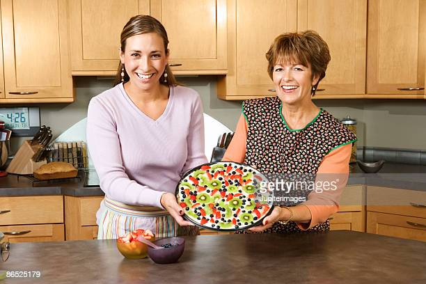 Mother and daughter holding dessert in kitchen