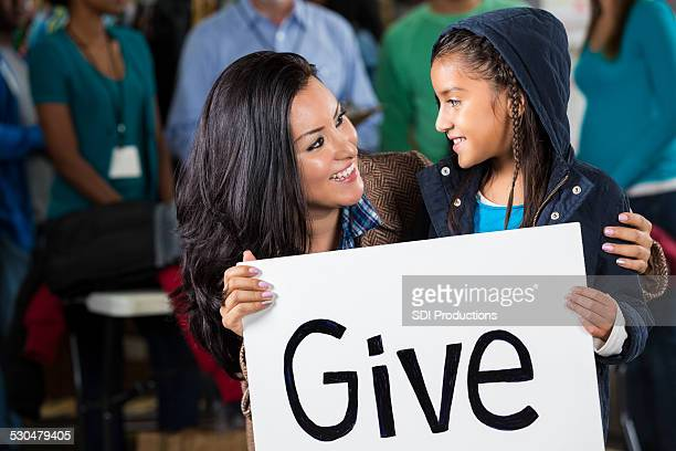Mother and daughter holding Give sign at clothing donation drive
