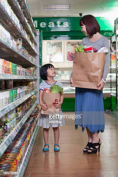 Mother and daughter holding grocery bags in supermarket, Beijing