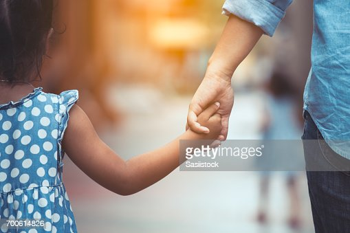 Mother and daughter holding hand together in vintage color tone : Stock Photo