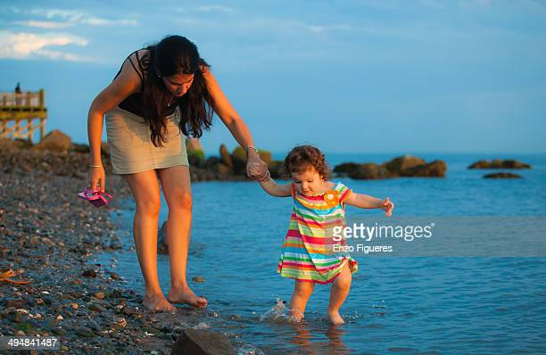 Mother and daughter holding hand while walking on the edge of the water