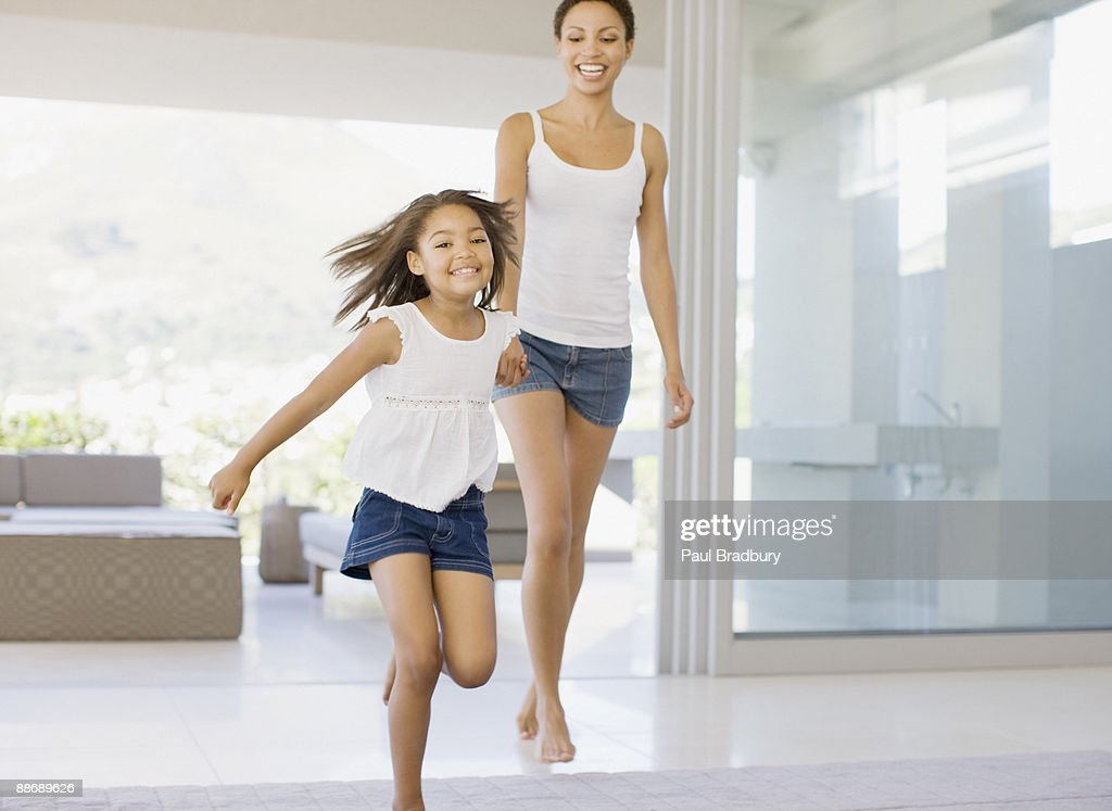 Mother and daughter holding hands and running